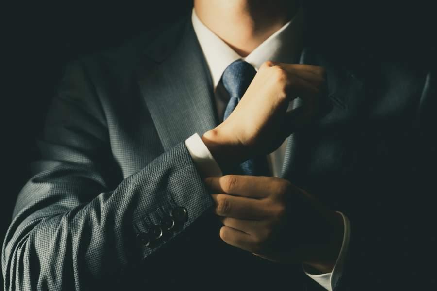 Mann in gestreiften Anzug mit Krawatte richtet sich seinen Ärmel und Manschettenknöpfe.