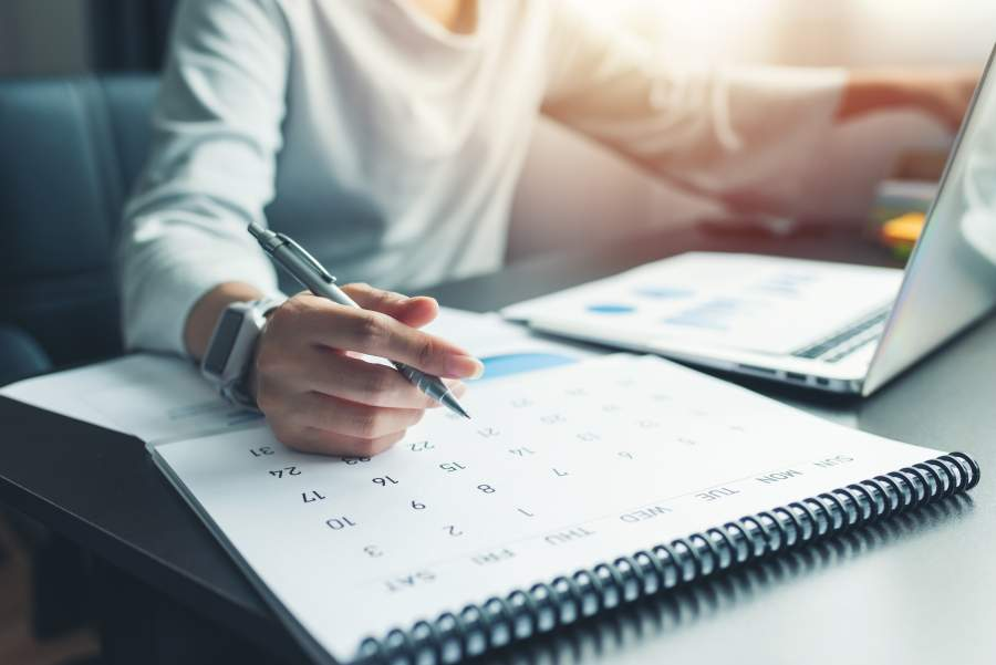 Frau sitzt mit Stift in der Hand vor Laptop und hat neben sich einen Terminkalender liegen.