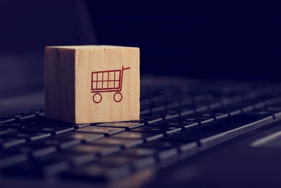 Ein Holzwürfel mit dunkelrotem Einkaufswagen-Icon liegt auf einer schwarzen Tastatur.