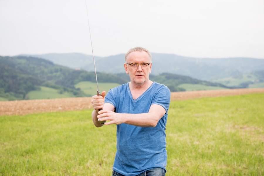 Klaus Rentel auf einer Wiese mit einem Schwert