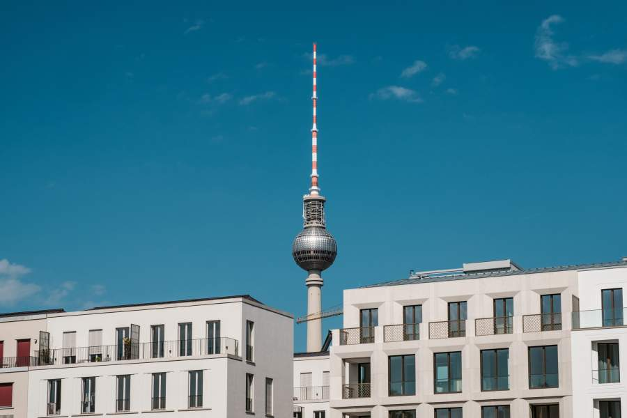 Im Vordergrund stehen zwei Gebäude, hinter denen der Fernsehturm in Berlin zu sehen ist.