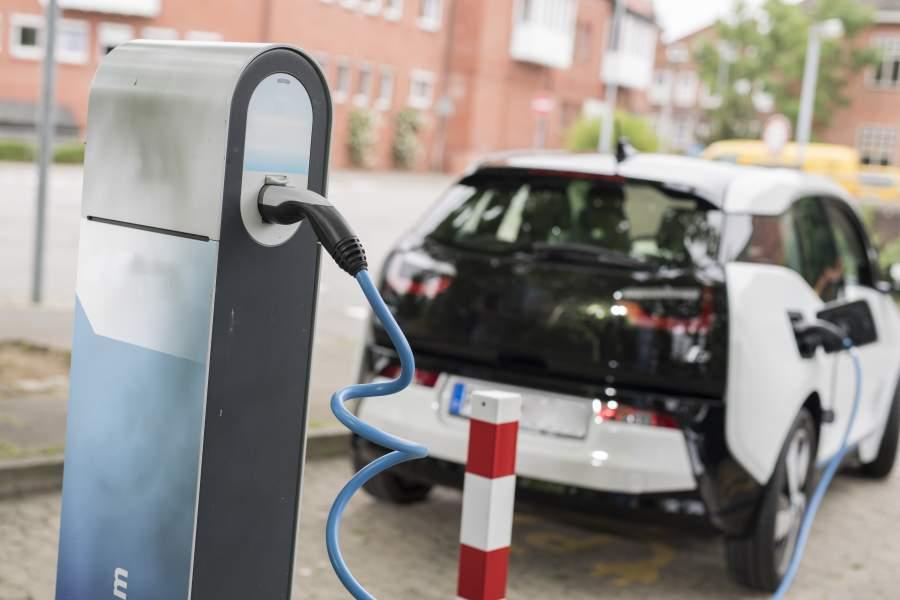 Ein schwarz-weißes Auto steht einer Ladestation und wird mit Strom betankt.