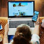 Frau sitzt mit Laptop auf dem Schoß und einem Smartphone in der rechten Hand auf einem Sofa und checkt ihre Social Media Accounts.