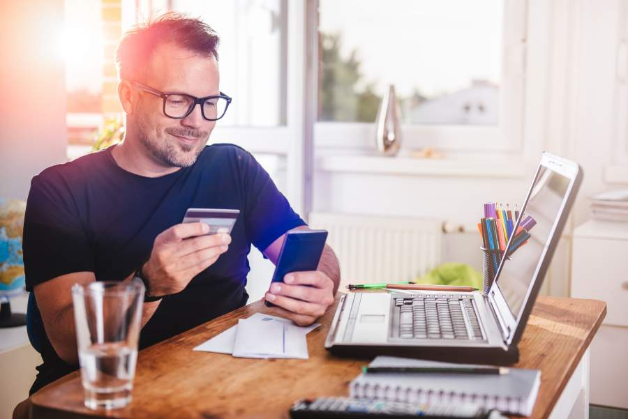 Mann sitzt lächelnd mit Smartphone und Kreditkarte in der Hand vor seinem Laptop am Schreibtisch.