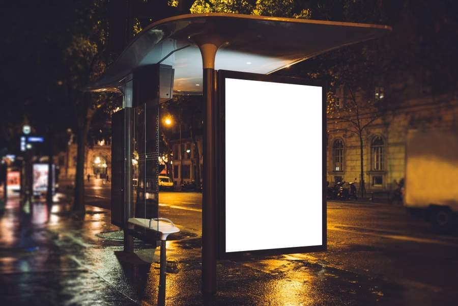 Eine leere Werbefläche für Außenwerbung an einer dunklen Bushaltestelle.