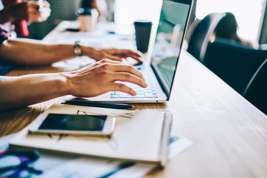 Jemand arbeitet an einem Laptop auf einem Tisch, daneben liegen ein Smartphone, ein Notizblock, Kaffeebecher