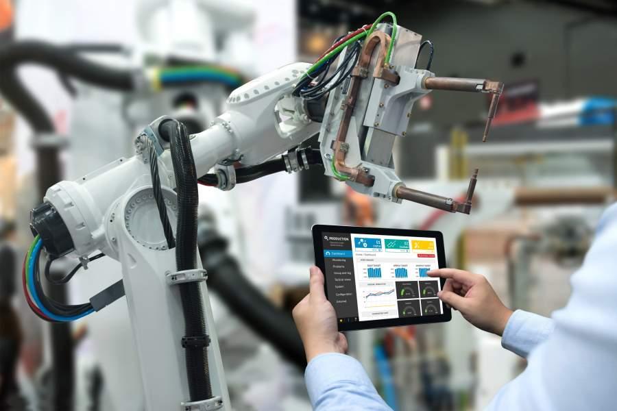 Mitarbeiter steuert einen intelligenten Industrieroboter über ein Tablet.