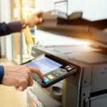 Mann steht am Laser-Drucker, um etwas zu kopieren und drückt den Start-Knopf.