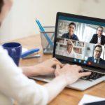 Geschäftsleute in einer Webkonferenz, Blick über die Schulter einer Teilnehmerin in Online-Meeting mit geteiltem Bildschirm mit vier weiteren Personen