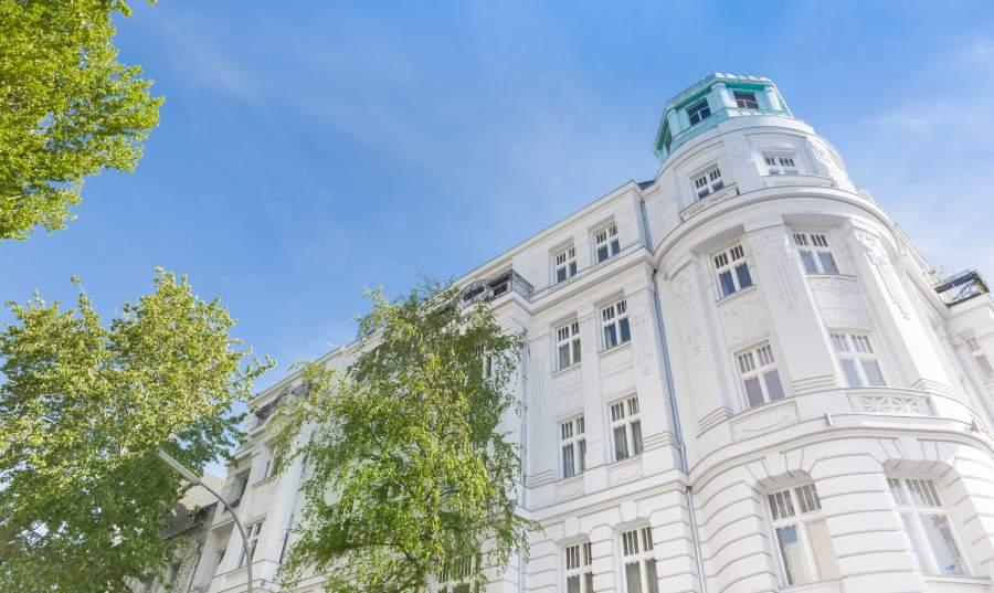 Drei Bäume vor der weißen Fassade eines Altbau-Apartments in der Stadt.