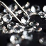 Einer von vielen weißen Diamanten auf schwarzem Hintergrund wird mit einer Pinzette angehoben