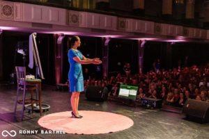 Körpersprache-Trainerin Yvonne de Bark mit Flipchart im Vortrag auf rotem, runden Teppich auf der Bühne