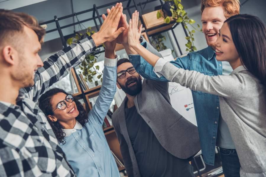 Fünf junge Mitarbeiter und Mitarbeiterinnen stehen zusammen in einem modernen Büro und geben sich ein gemeinsames High-Five.