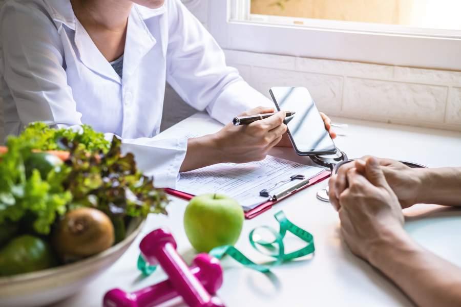 Ein weiblicher Gesundheitsberater berät seinen Kunden an einem Schreibtisch, auf dem sich Obst, Hanteln und ein Maßband befinden.