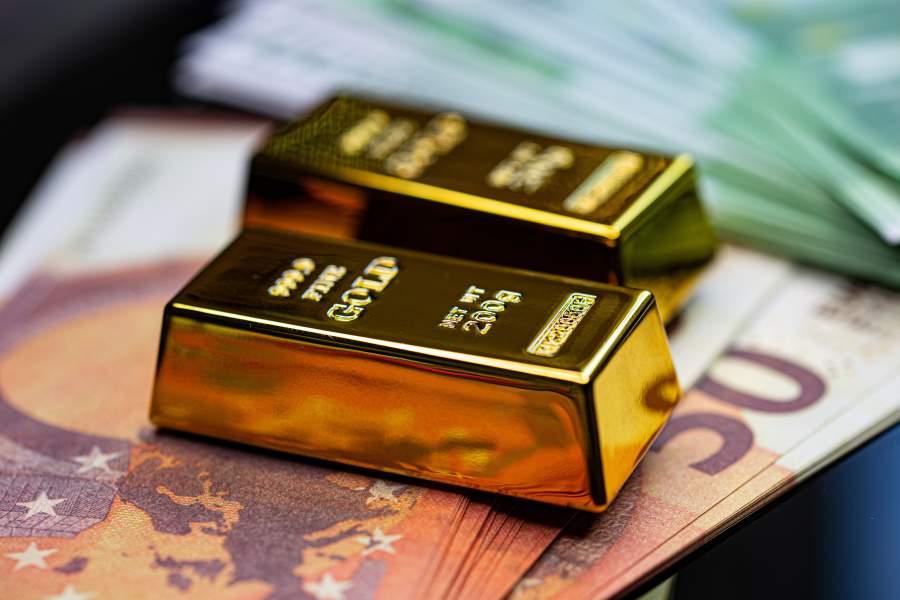 Zwei Goldbarren liegen auf einem Stapel Fünfzig-Euro-Scheinen neben einem Stapel von Hundert-Euro-Scheinen.