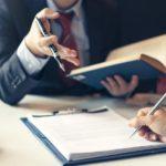 Geschäftsmann und Anwalt sitzen einander gegenüber und besprechen die Unterzeichnung eines Vertrags.