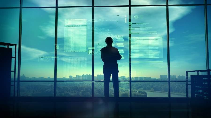 IT-Experte steht vor einer großen Fensterfront mit Blick über eine Stadt, auf der verschiedene Codeelemente zu sehen sind.