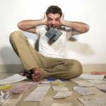 Verzweifelt Mann sitzt zwischen verschiedenen Dokumenten auf dem Boden, hält sich die Ohren zuhält und beißt in einen Taschenrechner.