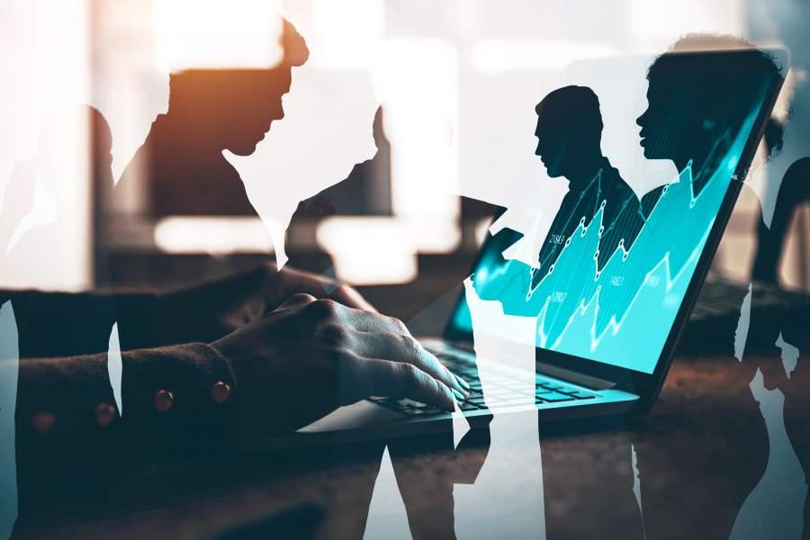 Frau sitzt vor Laptop und arbeitet als Trader während sich in einer Glascheibe andere Mitarbeiter spiegeln.