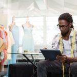Junger PoC-Mann sitzt mit Tablet in der Hand und Maßband um den Hals in einer Schneiderei oder Modeatelier.