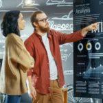 """Frau und Mann stehen vor einer Chart und interpretieren Diagramme, Schriftzu """"Analysis"""""""