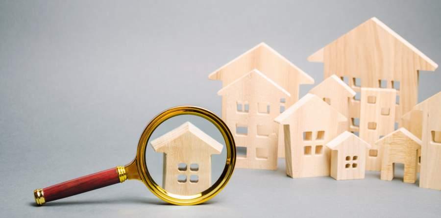 Holzfiguren von Häusern, eine Hausfigur ist durch eine Lupe zu sehen