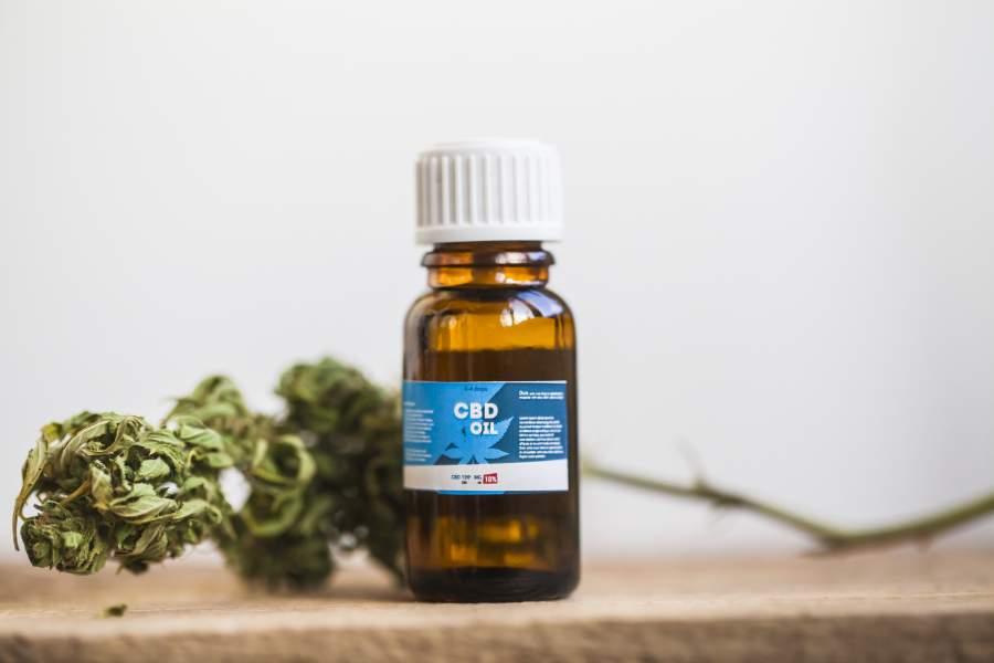Eine braune Flasche mit CBD-Öl seht neben einem sogenannten CBD Bud also einer Cannabisblüten.