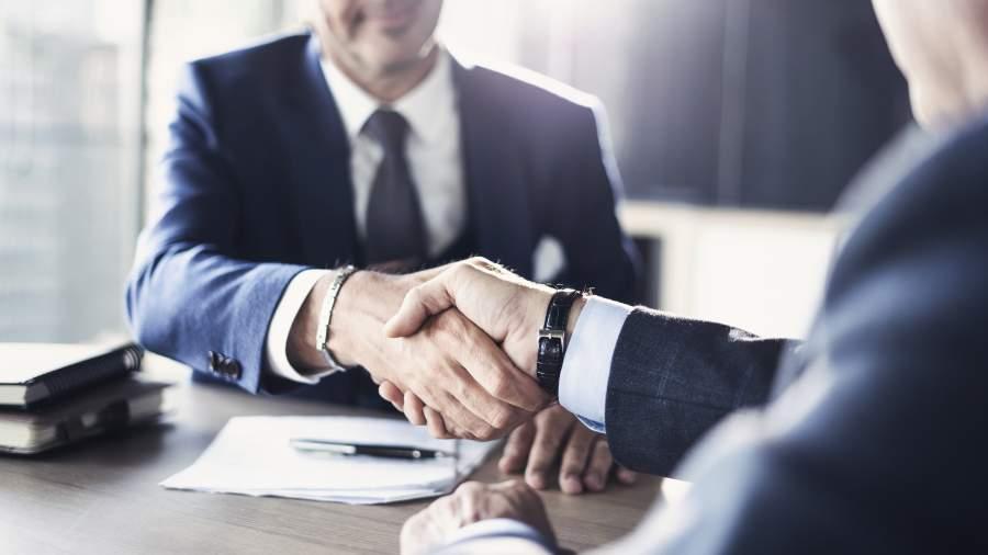 Zwei Geschäftspartner, deren Gesichter nicht zu sehen sind, schütteln sich die Hände