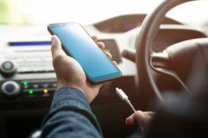 Mann steckt sein Handy während des Fahrens an ein Autoladegerät an.