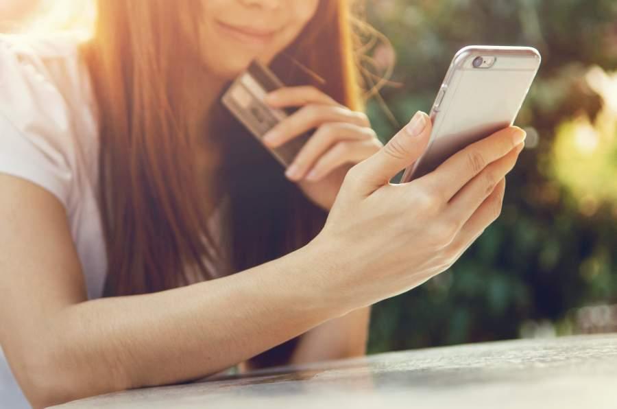 Junge Frau sitzt mit Smartphone und Kreditkarte in der Hand Draußen im Freien.