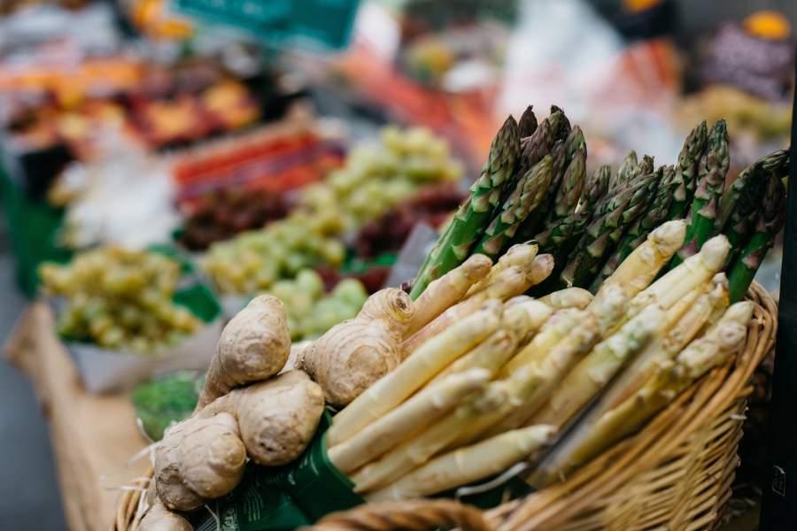 Korb gefüllt mit grünem Spargel, weißem Spargel und einer Ingwerknolle an einem Gemüsestand.