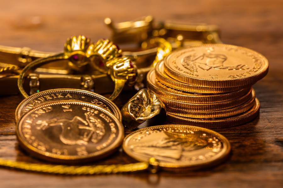 Alter Goldschmuck und alte geprägte Münzen in Stapeln liegen nebeneinander auf einem Holztisch.