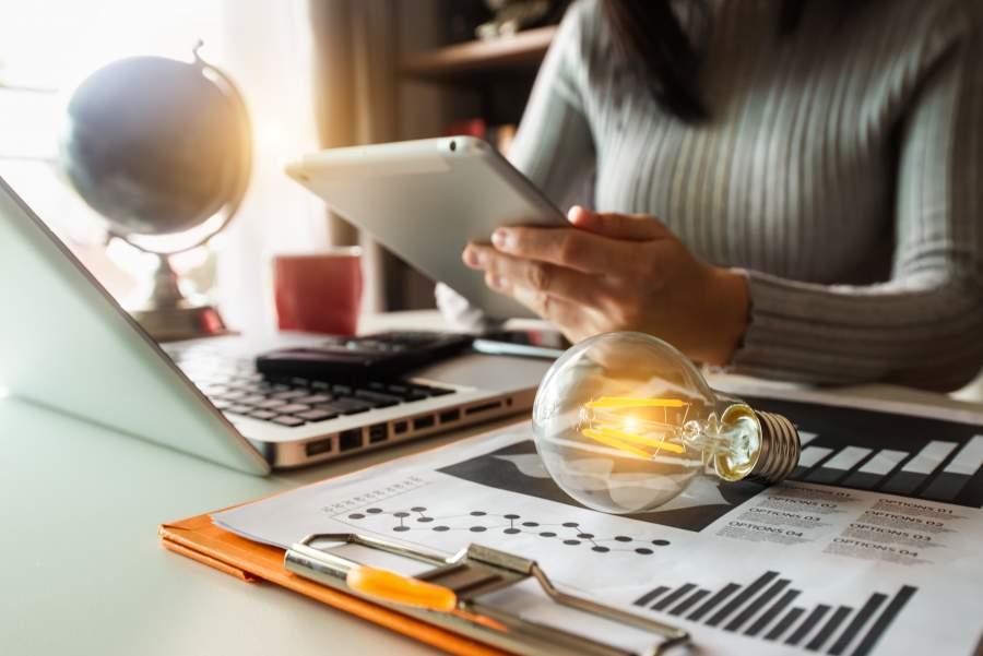 Frau sitzt an Schreibtisch mit Laptop, Smartphone, Tablet und Unterlagen, Globus, eine leuchtende Glühbirne im Vordergrund liegt auf Unterlagen mit Statistiken
