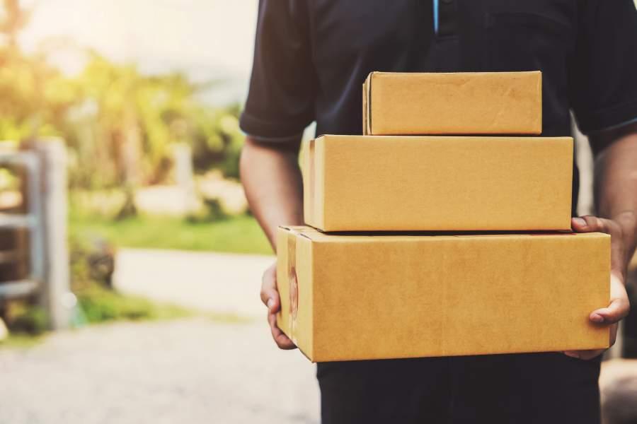 Postbote mit drei nach absteigender Größe aufeinandergestapelten Paketen in den Händen.
