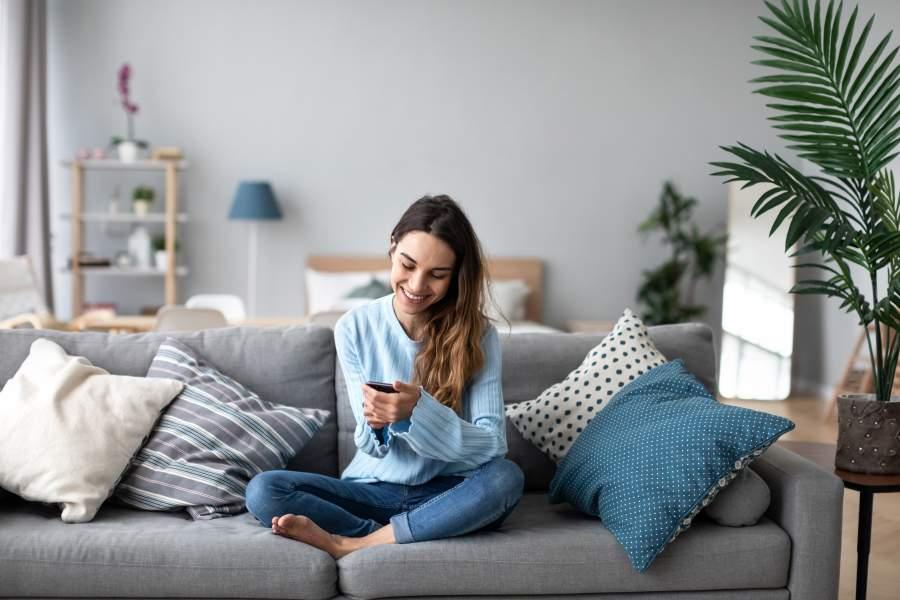 Junge Frau mit blauem Pullover und Jeans sitzt im Schneidersitz auf einem Sofa, das in einem modern eingerichteten Wohnzimmer steht, und sieht in ihr Handy.