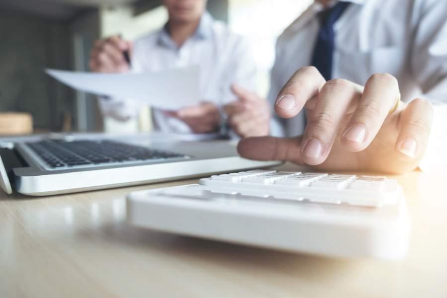 Zwei Geschäftsmänner an Tisch arbeiten mit Laptop, Unterlagen und Taschenrechnern