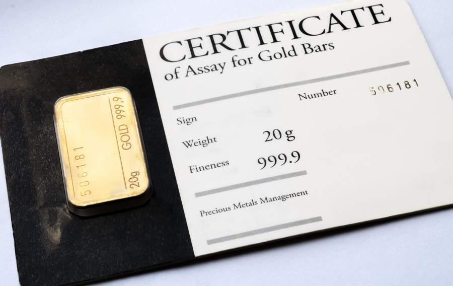 Ein 20 Gramm Minibarren Gold liegt zusammen mit einem Zertifikat in einer Schutzhülle auf dem Tisch.