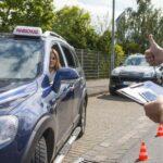 Fahrlehrer gibt Fahrschülerin in Auto Anweisungen, Umfahren von Pylonen