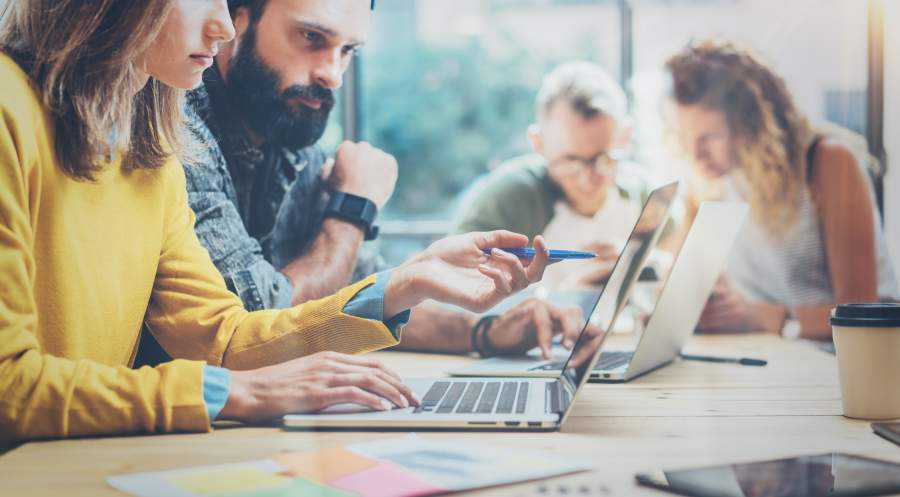 Nahaufnahme von zwei Frauen und zwei Männern, die in zwei gemischten Gruppen an einem Schreibtisch vor einem Laptop zusammensitzen und jeweils etwas gemeinsam besprechen.