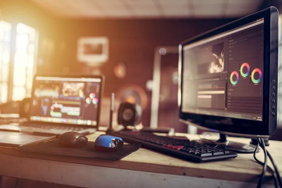 Ein Laptop und ein Bildschirm mit Computermaus und Tastaturen stehen auf einem Schreibtisch und zeigen geöffnete Videobearbeitungsprogrammen.