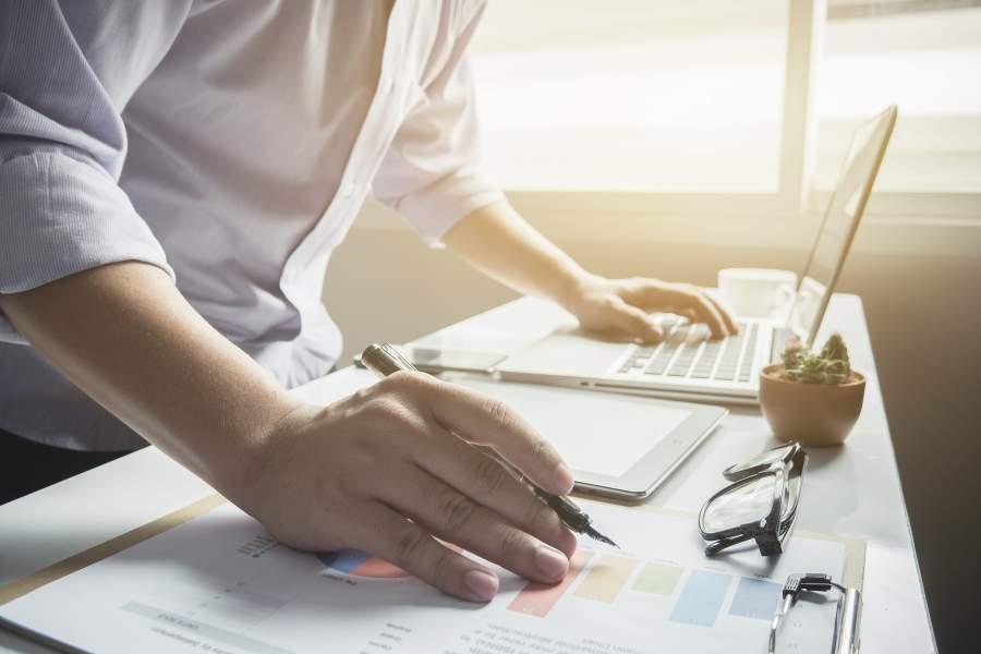Ein Mann in grauem Hemd steht im Büro vor seinem Schreibtisch mit einer Hand auf dem Laptop während er mit der anderen Hand etwas auf einen Notizblock überträgt.