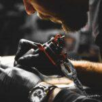 Tätowierer mit Gummihandschuhen und Tätowier-Maschine beim Stechen eines Tattoos
