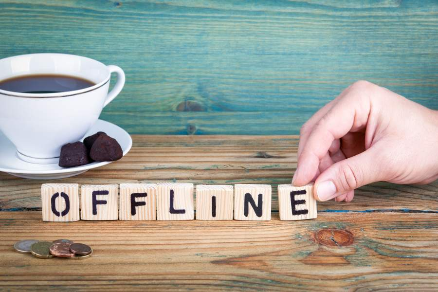 Schriftzug OFFLINE auf Holzwürfeln mit einer menschlichen Hand am letzten Buchstaben, Kaffeetasse und Holztisch im Hintergrund