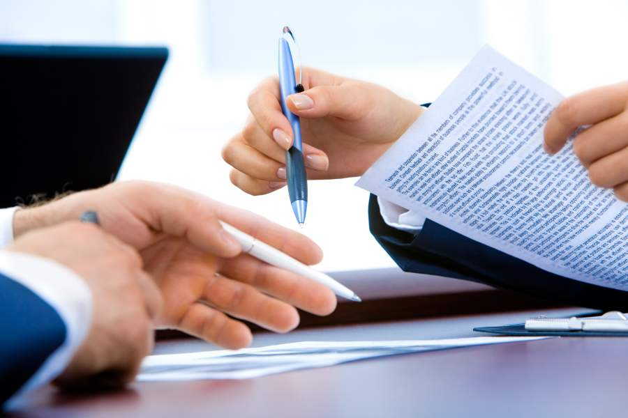 Die Hände zweier Geschäftsleute mit Kugelschreibern und Dokumenten in der Hand während einer Besprechung.