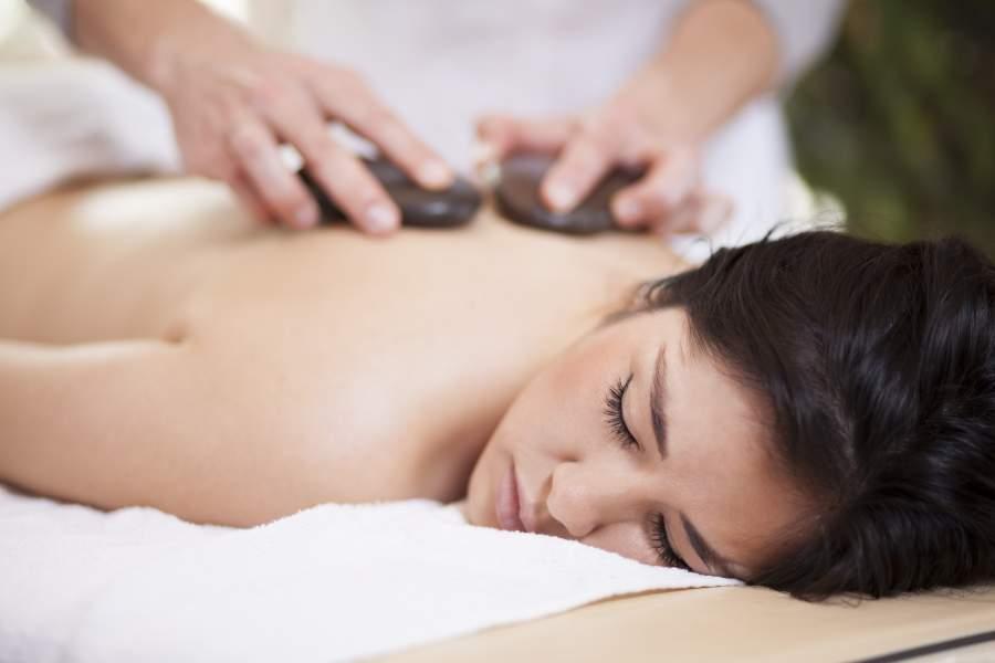 Junge Frau liegt auf einer Massageliege während sie eine Warmsteinmassage bekommt.