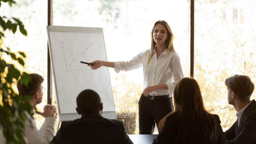 Eine seriös gekleidete Frau mit weißer Bluse steht an einer Flipchart vor einer Gruppe von Leuten und erklärt diesen etwas.