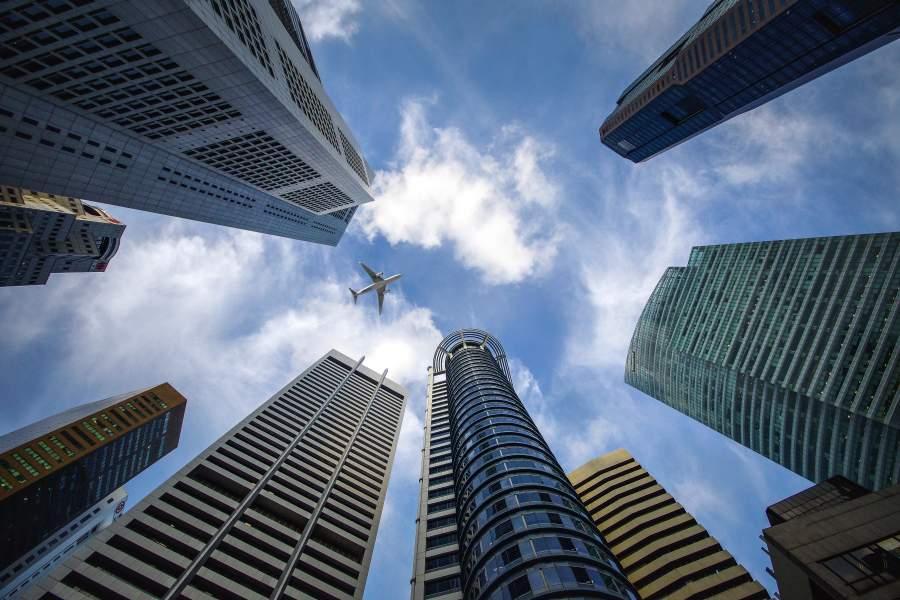Flugzeug üer großen Bürogebäude-Hochhäusern vor wolkigem Himmel
