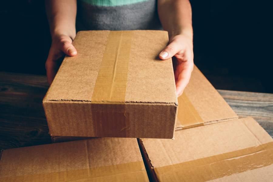 Frau hält ein Paket in der Hand, unter dem drei weitere Pakete zum Vorschein kommen