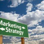 Ein grünes Straßenschild in der Wüste vor einem blauen Himmel, welches mit Marketing und Strategie als unterschiedliche Richtungen beschriftet ist.