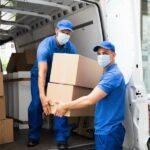 Zwei blau angezogene Mitarbeiter eines Umzugsunternehmens mit Mund-Nasen-Schutz laden Kartons aus einem Transporter aus.
